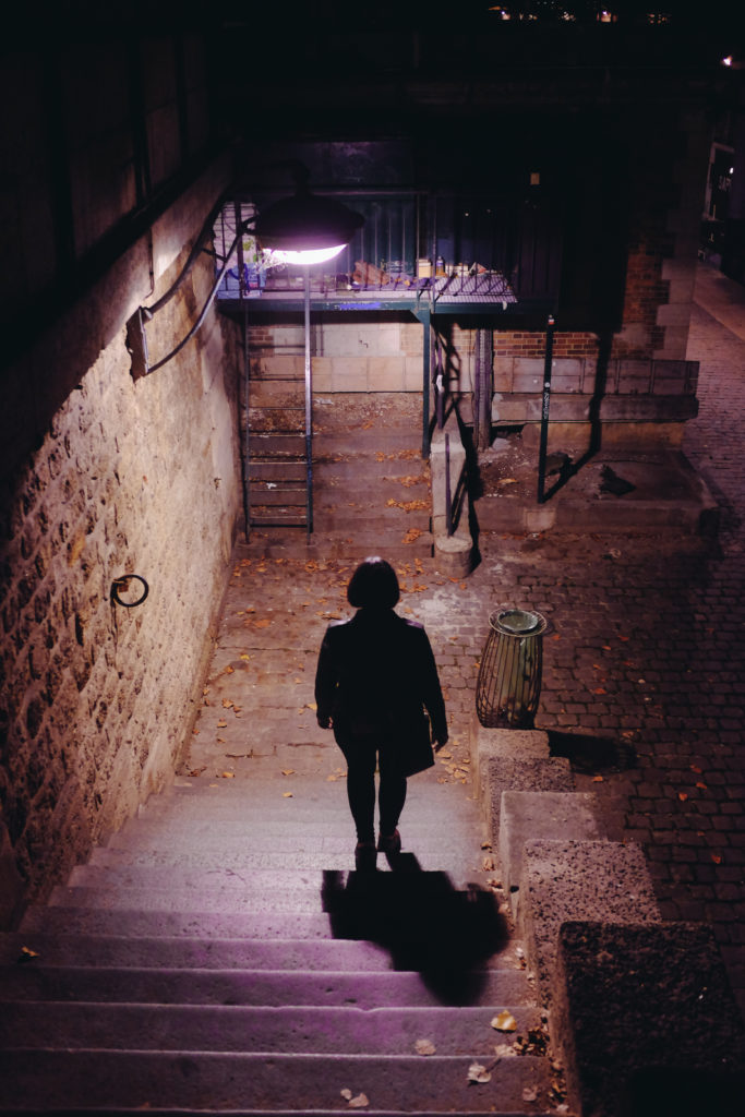 girl descending stairs to the seine at night